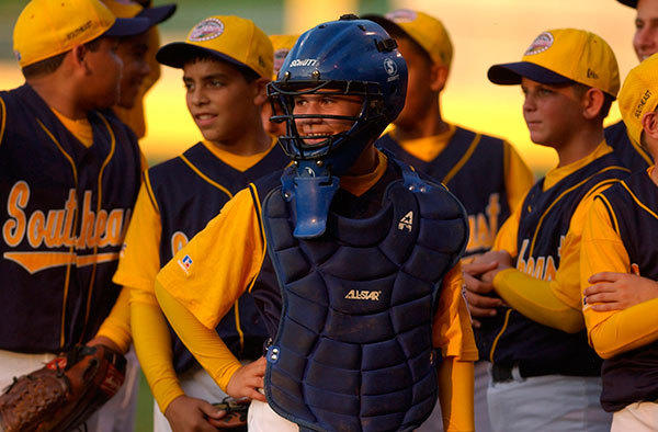 Catcher Andrew Weaver and the rest of the East Boynton Beach Little League team watches the pre-game festivities before their first game in the Little League World Series.  Weaver injured his hand early in the game, and the extent of the injuries are unknown.