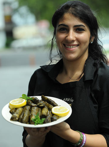 Serena Younes holds a plate of stuffed grape leaves at her family's Aladdin Restaurant in Allentown.