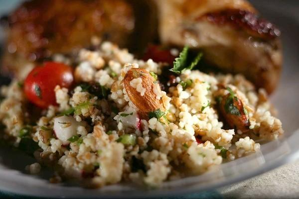 Houston's couscous is made with couscous, bulgur wheat, radishes, parsley, green onions, raisins, tomatoes, almonds and mint.