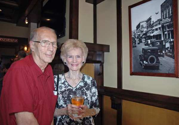 Les Rosenberg, former owner of the Photo Art Shop, with Mary Jane Strickland, founder of the Gordon R. Howard Museum, during the grand opening of Story Tavern. They are looking at a photograph of Story Hardware taken by Rosenberg's father, Rudy Rosenberg.