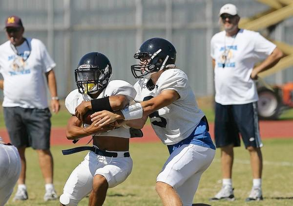 Marina High quarterback Austin Sojke (9) hands the ball off to Eli Cabaccang (1) during practice on Tuesday.