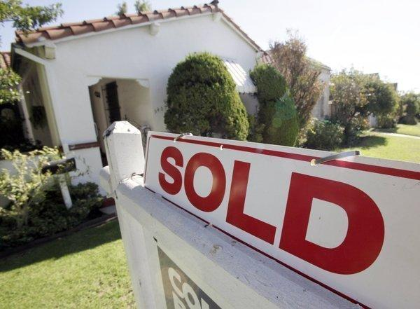 "A ""sold"" sign is seen outside a home in Los Angeles."
