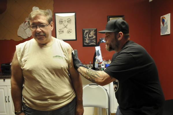 Brooklyn Payne, a tattoo artist from Allentown, Pa., (right) applies an outline of a portrait on Charlie Miller's (left) arm in preparation for a tattoo. Miller, of Weymouth, Massachusetts, was having a portrait of his later sister, Sandy, tattooed by Payne, a well-known portrait artist, at at Tommy's Tattoo Studio in East Windsor Wednesday afternoon. Payne will be appearing at this weekend's tattoo convention at the Connecticut Convention Center.