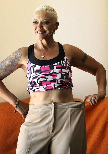 Charlene Casey, who lost 74 pounds since November when she began working out and eating a strict diet, tries on an old pair of pants at her home in Carson on Friday, August 3, 2012.