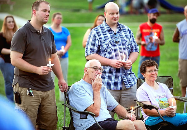 "James Ulrich, left, and his brother, Timothy Ulrich, right, stand behind their father, Joseph Ulrich, and their stepmother, Rose Ulrich, Wednesday night during a candlelight vigil for Joseph Alexander ""Alex"" Ulrich Jr. at Smithsburg's Veterans Park."