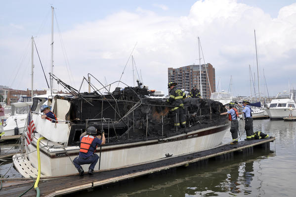 Firefighters respond to a fire Wednesday afternoon aboard a 40-foot cabin cruiser at the Anchorage Marina near the 2500 block of Boston Street in Canton.