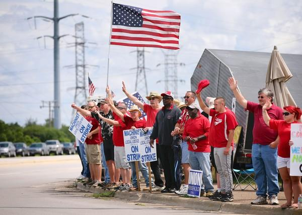 Before Gov. Quinn's visit Friday, striking union workers shout at replacement workers outside a Caterpillar plant in Joliet.