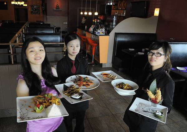 Bangkok Thai manager Jenny Chen (left) holds Mango Tofu and Chicken Satay. Waitress Emily Yang (center) holds Grill Shrimp Satay and Thai Mini Spring Rolls. Waitress Sofia Shi (right) holds Yellow Curry and Coconut Shrimp.