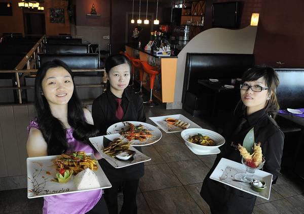 Bangkok Thai manager Jenny Chen (left) holds Mango Tofu and Chicken Satay. Waitress Emily Yang (center) holds Grill Shrimp Satay and Thai Mini Spring Rolls. Waitress Sofia Shi (right) holds Yellow Curry and Coconut Shrimp.
