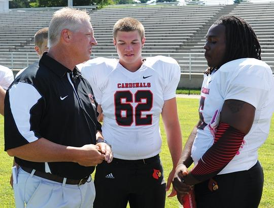 George Rogers Clark football coach Steven Collins chats with seniors Robert Cornelius, right, and Aaron Redmon (62) during the team¿s picture day earlier this month at Cardinal Stadium. Collins and the Cardinals open the season Friday night at Corbin. Kickoff is set for 7:30 p.m.