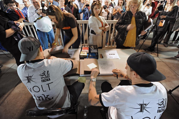 Chefs Bryan, left, and Michael Voltaggio, right, of Bravo TV's Top Chef, autographed books for fans during VOLTink Night at Harry Grove Stadium in Frederick. The brothers launched their collaborative cook book VOLT ink