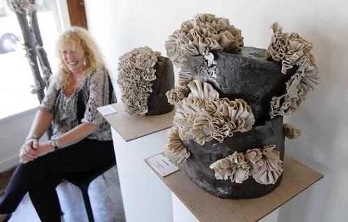"Ceramist Robin Lee Riddell sits next to ""Mad Hatter,"" right, at the new Forest and Ocean Gallery in Laguna Beach."