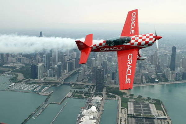 Aerobatic pilot Sean D. Tucker, left, flies Chicago firefighter Steve O'Malley, who rescued a baby from drowning at the 31st Street Harbor Aug. 4, in Team Oracle's Extra 300 during media preview day for the Chicago Air & Water Show at the Gary Jet Center.