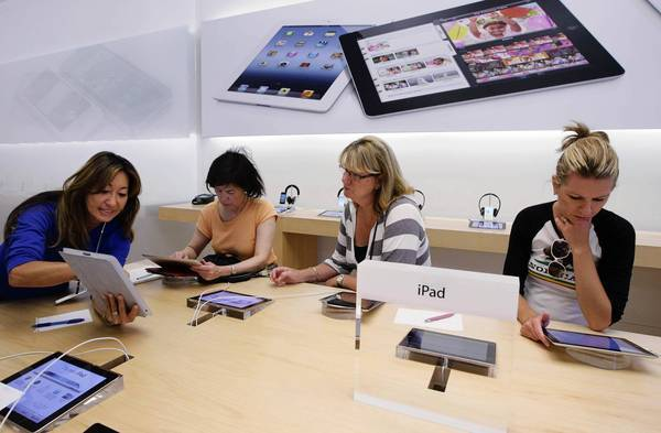 Apple's stores are heralded for their clean, spacious design and minimalist architecture. Much of their success is attributed to knowledgeable employees who are widely available but not overly pushy. Above, an Apple worker, left, gives an iPad tutorial to customers in Palo Alto.