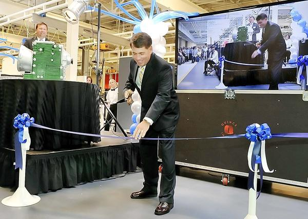 Ron Hubers, Volvo Trucks President of North American sales and marketing cuts a ribbon for the new transmission assembly line at Volvo Plant in Hagerstown on Thursday.