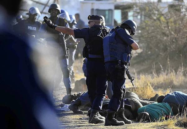 South African police check the bodies of striking workers shot at a platinum mine near Marikana, 40 miles northwest of Johannesburg.