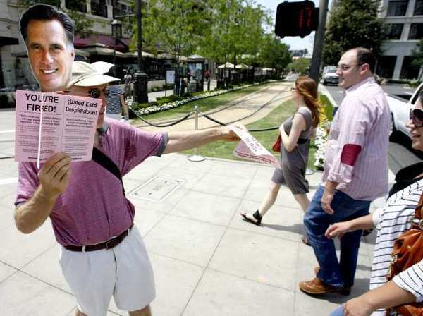 "Mark S. of Moveon.org passes out ""You're Fired"" pamphlets to passersby at the Americana at Brand in Glendale. About 10 protesters were at both entrances to the outdoor shopping venue."