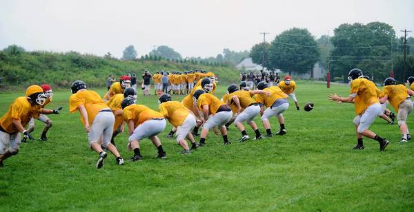 The Bangor High School football team practices on a field behind the high school Tuesday. August 14, 2012.