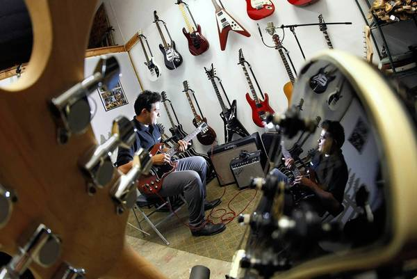 Erik Jimenez, owner of Belongingsbroker Music Center, tests a guitar. The Bellflower resident borrowed money from microlender Kabbage to buy 200 used guitars that he could sell through his online store.