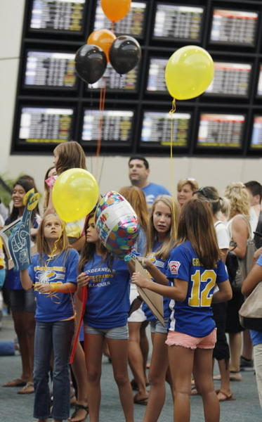 Fans wait patiently in the terminal area as they await the arrival of the Windermere Little League softball team at Orlando International Airport on Thursday, August 16, 2012. The team was returning from Portland, Oregon, where they lost in the championship game of the World Series.