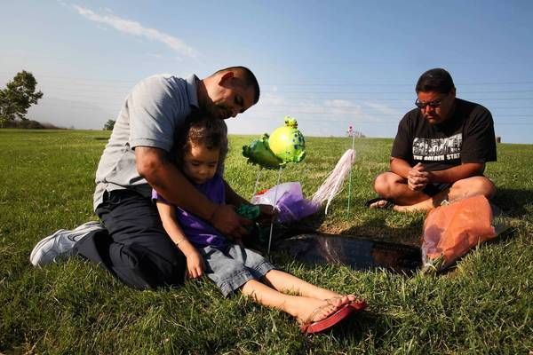 Jose Vasquez holds daughter Angie, 3, as he sits with brother Raymond Vasquez at the grave of their sister Tayde Vasquez at Rose Hills Memorial Park in Whittier. Tayde was shot to death 20 years ago, when she was 13 years old.