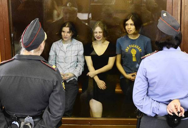 "Members of the all-girl punk band ""Pussy Riot"" Yekaterina Samutsevich, left,, Maria Alyokhina, center, and Nadezhda Tolokonnikova sit in a glass-walled cage during a court hearing in Moscow. A Moscow court found the three women from a tiny punk band guilty of defying the Russian authorities and ridiculing President Vladimir Putin in a church. Pussy Riot release rallies have stretched from Sydney to New York as a growing list of celebrities joined ex-Beatle Paul McCartney and pop icon Madonna in a campaign directed against Putin's crackdown on most dissent."