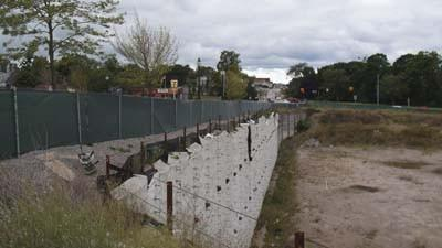 The retaining wall along the dormant Petoskey Pointe construction site's perimeter is seen today, Friday, looking west from the corner of Mitchell and Petoskey streets.