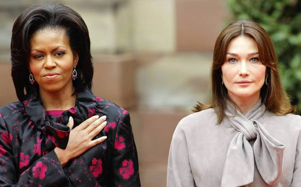 First lady Michelle Obama (left), contrary to Internet accounts, places her hand over her heart during the U.S. national anthem in 2009. French first lady Carla Bruni does not, as is completely proper.