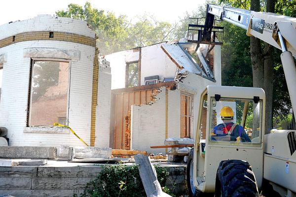 A section of the old McEldowney building crashes down with a push from a lift operated by Iliz Hechaber Thursday, top photo. The building on South Main Street once was one of the most ornate buildings in Winchester, but has been deteriorating for many years. Workers Pollo Natanael, left, and Hechaber salvage one of the stone headers from above one of the windows, bottom photo. The building was once part of the Guerrant Mission Clinic and Hospital. The other building, owned by the Guerrants, is now the home of the Bluegrass Heritage Museum. Most, if not all, of the building, is expected to be down by this afternoon.