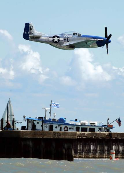 A World War II-era P-51 Mustang fighter cruises over Lake Michigan during a rehearsal for the Chicago Air and Water Show.