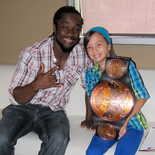 Kofi Kingston lets Hannah Mitchell hold one of the WWE tag team championship belts.