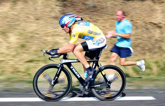 A fan runs by US Lance Armstrong