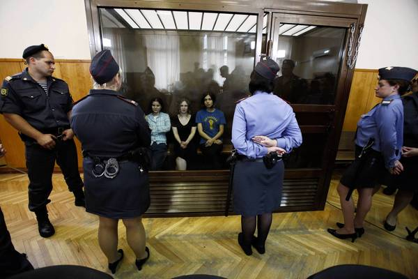 Members of the Russian punk band Pussy Riot, from left, Yekaterina Samutsevich, Maria Alekhina and Nadezhda Tolokonnikova, sit in a glassed-in dock of a Moscow courtroom as they await the verdict in their case.