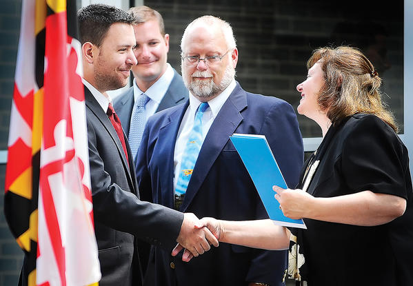 Pittsburgh Institute of Aeronautics graduate Kyle Collins, left, shakes hands with PIA Admissions Representitive Roxanne Ober Friday afternoon during PIA-Hagerstown's first ever graduation ceremony held at the Hagerstown/Washington County Regional Airport. At rear is John Graham III President and CEO of PIA and Thomas O'Keefe Campus Director at right.