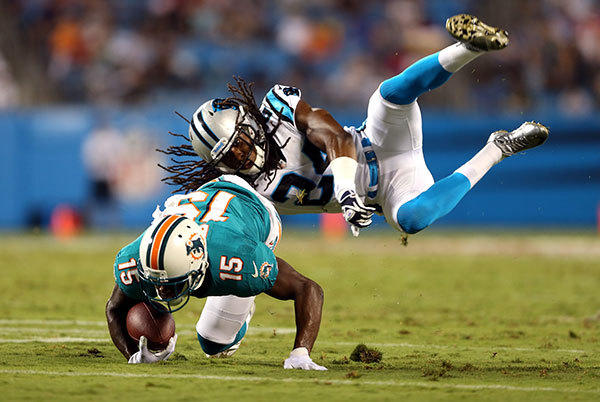 Josh Norman #24 of the Carolina Panthers dives for  Davone Bess #15 of the Miami Dolphins during their preseason game at Bank of America Stadium on August 17, 2012 in Charlotte, North Carolina.