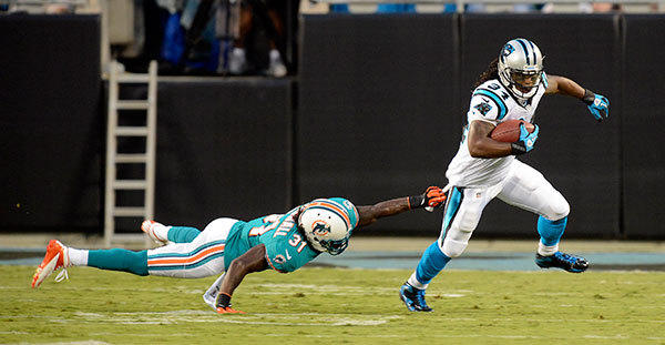 Carolina Panthers running back DeAngelo Williams (34) avoids the tackle by Miami Dolphins defensive back Richard Marshall (31) during the first quarter at Bank of America Stadium.