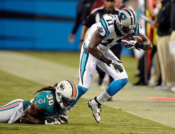 Carolina Panthers wide receiver Brandon LaFell (11) works to gets a few more yards after a reception as the Miami Dolphins' Chris Clemons (30) works to bring him down in the first half on Friday, August 17, 2012, at Bank of America Stadium in Charlotte, North Carolina.