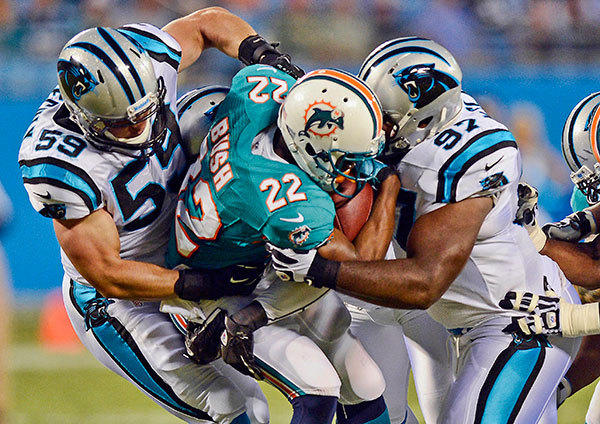The Carolina Panthers' Luke Kuechly (59) and  Terrell McClain (97) team up to bring down Miami Dolphins running back Reggie Bush (22) in the first half on Friday, August 17, 2012, at Bank of America Stadium in Charlotte, North Carolina.