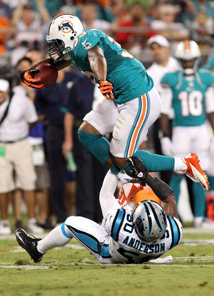 Miami Dolphins running back Daniel Thomas (33) jumps over Carolina Panthers linebacker James Anderson (50) during the second quarter at Bank of America Stadium.