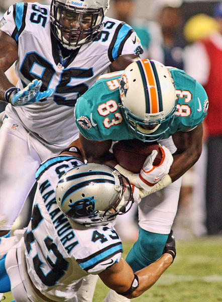 Miami Dolphins wide receiver Jeff Fuller (83) gets tackled by Carolina Panthers defensive back Haruki Nakamura (43) during the second quarter at Bank of America Stadium.