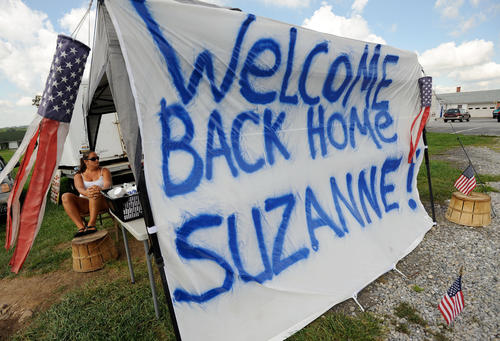 Kristina Foderaro of White Marsh mans a crab stab with a sign welcoming home Olympic pentathlete Suzanne Stettinius of Parkton before a welcome parade on York Road in Parkton.