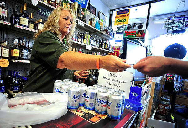 Julie Fitz checks a customer's identification for a beer purchase Tuesday morning at Roxy Liquors at Kenley Square shopping center.