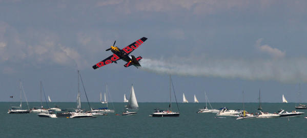 A member of the Red Bull flight team performs a low pass over Lake Michigan during the Chicago Air and Water Show at North Avenue Beach.