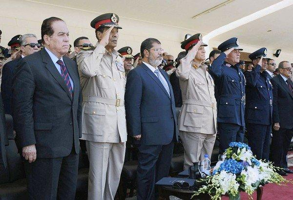 In a July ceremony at an air force base in Cairo, Egyptian President Mohamed Morsi is flanked by Field Marshal Mohamed Hussein Tantawi, left, and Lt. Gen. Sami Anan. Morsi has since dismissed Tantawi as defense minister and military commander and Anan as military chief of staff.