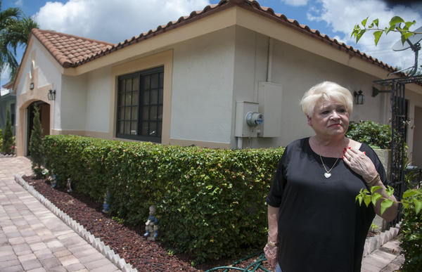 Diana Latzko, a Citizens policyholder in Davie, outside her home. Latzko, an avid record keeper, kept all of her records, permits and even the stickers on her windows to prove full compliance to hurricane codes to the Citizens inspector.