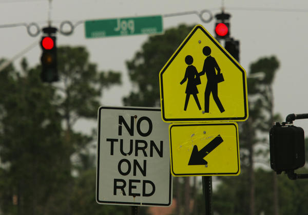 "A ""No Turn on Red"" sign sits on a post instead of hanging from the wire near signal lights."
