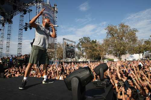 The crowd cheers on Common as he performs during the first day of Rock the Bells at the San Bernardino Nos Events Center.
