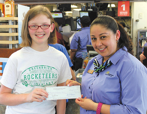 Greenbrier Elementary School student Kensie Olson, left, presented a check to Lucy Samoyoa at McDonald's on Dual Highway.
