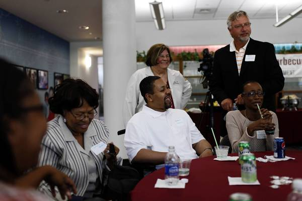 Claria Searcy, left, and her son Robert Searcy chat with trauma nursing chief Jan Gillespie, in white coat, and White Sox star Ron Kittle, right.