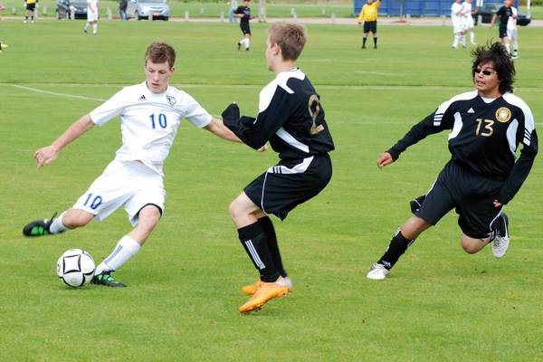 Burt Lake Northern Michigan Christian Academy sophomore Ben Vinz (10) clears the ball away from Harbor Springs' Casey Cousins (middle) and Geraldo Silva during Friday's NMCA Soccer Invitational at the Click Road Soccer Complex.
